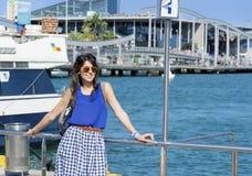 Jeune femme de sourire avec les lunettes de soleil d'or se reposant sur une jetée de mer à Barcelone photo stock