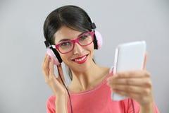 Jeune femme de sourire avec les lunettes rouges écoutant la musique Photos libres de droits