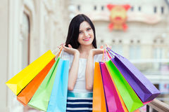 Jeune femme de sourire avec les paniers colorés des boutiques de fantaisie Photo stock