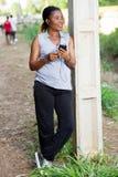 Jeune femme de sourire avec un téléphone portable photographie stock libre de droits