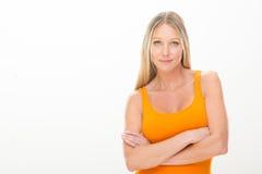 Jeune femme de sourire blonde avec la robe orange d'isolement sur le blanc Photographie stock libre de droits