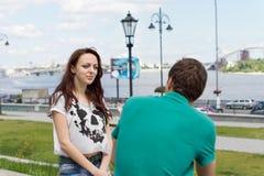 Jeune femme de sourire causant à un ami masculin Photographie stock libre de droits