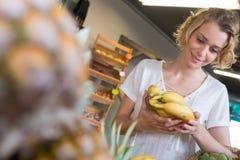 Jeune femme de sourire choisissant des bananes de épicerie photos libres de droits