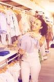 Jeune femme de sourire choisissant des vêtements de bébé bleu Photographie stock libre de droits