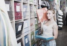 Jeune femme de sourire choisissant l'ensemble de literie de tissu Photo stock
