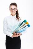 Jeune femme de sourire d'affaires en verres tenant des dossiers avec des documents Images stock