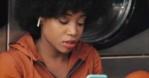 Jeune femme de sourire d'Afro-am?ricain ? l'aide du smartphone ? la laverie automatique Elle ?coutent musique et chant Libre serv clips vidéos