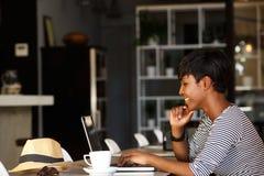 Jeune femme de sourire d'afro-américain travaillant sur l'ordinateur portable image libre de droits