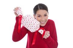 Jeune femme de sourire d'isolement en rouge tenant un présent avec le coeur Photographie stock libre de droits