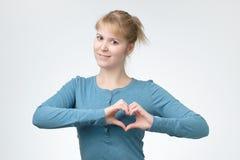 Jeune femme de sourire dans la chemise bleue montrant le geste de coeur avec deux mains photo libre de droits
