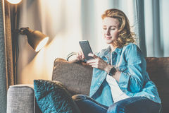 Jeune femme de sourire dans la chemise de denim se reposant à la maison sur le divan et à l'aide du smartphone La fille utilise l photographie stock libre de droits