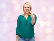 Jeune femme de sourire dans la chemise montrant des pouces  Photographie stock