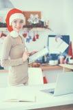Jeune femme de sourire dans la cuisine, d'isolement sur le fond de Noël Photos stock
