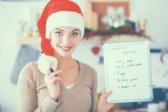 Jeune femme de sourire dans la cuisine, d'isolement sur le fond de Noël Photo stock