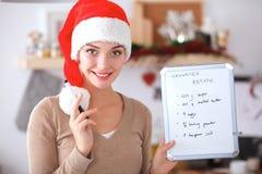 Jeune femme de sourire dans la cuisine, d'isolement sur le fond de Noël Photo libre de droits