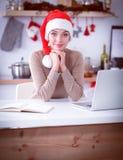 Jeune femme de sourire dans la cuisine, d'isolement sur le fond de Noël Image libre de droits