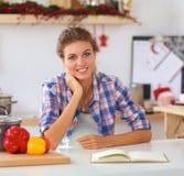 Jeune femme de sourire dans la cuisine, d'isolement sur le fond de Noël Image stock