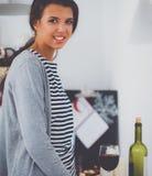 Jeune femme de sourire dans la cuisine, d'isolement sur le fond de Noël Images libres de droits