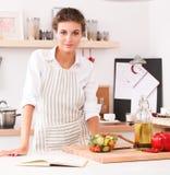 Jeune femme de sourire dans la cuisine, d'isolement sur le fond de Noël Images stock