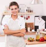 Jeune femme de sourire dans la cuisine, d'isolement sur le fond de Noël Photographie stock