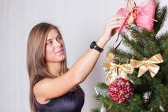 Jeune femme de sourire dans la robe élégante décorant l'arbre de Noël photo stock