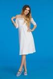 Jeune femme de sourire dans la robe blanche d'été et des espadrilles rayées Image stock