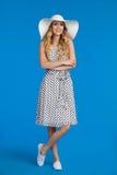 Jeune femme de sourire dans la robe d'été, les espadrilles et le chapeau blanc de Sun Photographie stock libre de droits