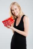 Jeune femme de sourire dans la robe noire tenant le boîte-cadeau Photo libre de droits