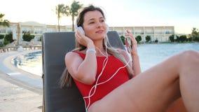 Jeune femme de sourire dans le bikini rouge et musique blanche d'écouteurs dansant et d'écoute de son smartphone, tout en se trou clips vidéos