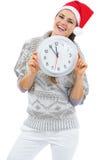 Jeune femme de sourire dans le chandail et le chapeau de Noël montrant l'horloge Photo stock