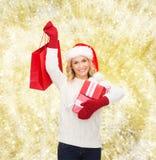 Jeune femme de sourire dans le chapeau d'aide de Santa avec des cadeaux Images stock