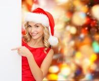 Jeune femme de sourire dans le chapeau de Santa avec le conseil blanc Images stock