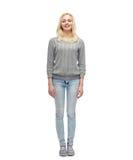 Jeune femme de sourire dans le pull et des jeans gris Images libres de droits