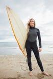 Jeune femme de sourire dans le vêtement isothermique tenant la planche de surf à la plage Photos stock