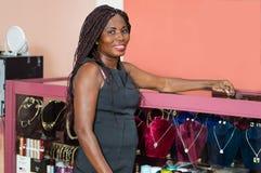 Jeune femme de sourire dans son magasin de bijoux image libre de droits