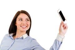 Jeune femme de sourire de brune prenant un autoportrait avec son pho image stock