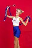 Jeune femme de sourire de charme dans la jupe bleue en verre drôles avec le bl Photos stock