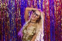 Jeune femme de sourire de charme dans le club avec les cheveux blonds sur l'habit bariolé Image stock