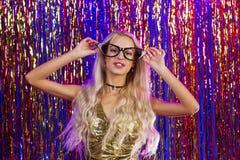 Jeune femme de sourire de charme dans le club avec les cheveux blonds sur l'habit bariolé Photos libres de droits