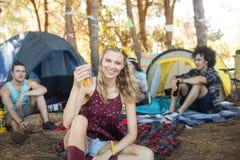 Jeune femme de sourire de portrait tenant le verre de bière au terrain de camping Photo libre de droits