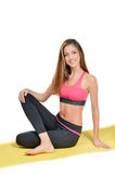 Jeune femme de sourire et de regard heureuse d'appareil-photo faisant le yoga sur le tir de studio de tapis Images libres de droits