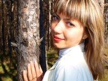 Jeune femme de sourire et un arbre de pin photos stock