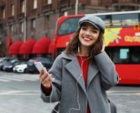 Jeune femme de sourire faisant appel et parlant au smartphone dans la ville d'automne image libre de droits