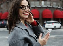 Jeune femme de sourire faisant appel et parlant au smartphone dans la ville d'automne photographie stock libre de droits