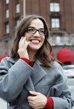 Jeune femme de sourire faisant appel et parlant au smartphone dans la ville d'automne photographie stock