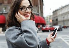 Jeune femme de sourire faisant appel et parlant au smartphone dans la ville d'automne images stock