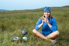 Jeune femme de sourire faisant cuire sur une cuisinière à gaz photos stock