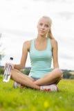 Jeune femme de sourire faisant la pause sur l'herbe Photo stock