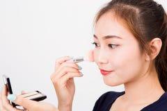 Jeune femme de sourire heureuse avec la brosse de cosmétiques photographie stock libre de droits