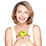 Jeune femme de sourire heureuse avec la pomme verte. Photo libre de droits